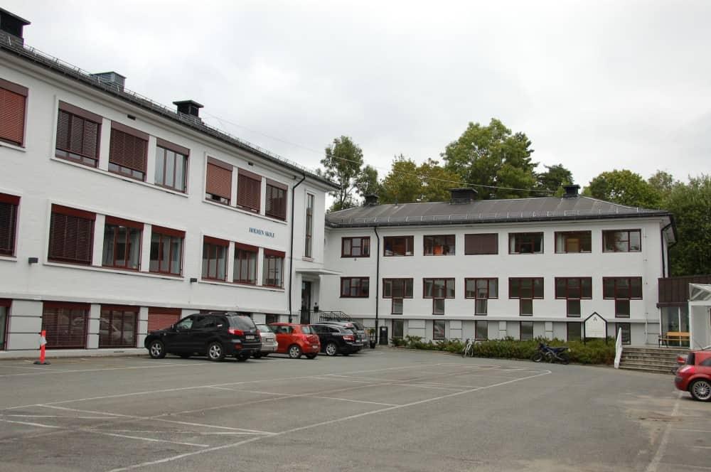 Næringsbygg hvit fasade med parkeringsplass